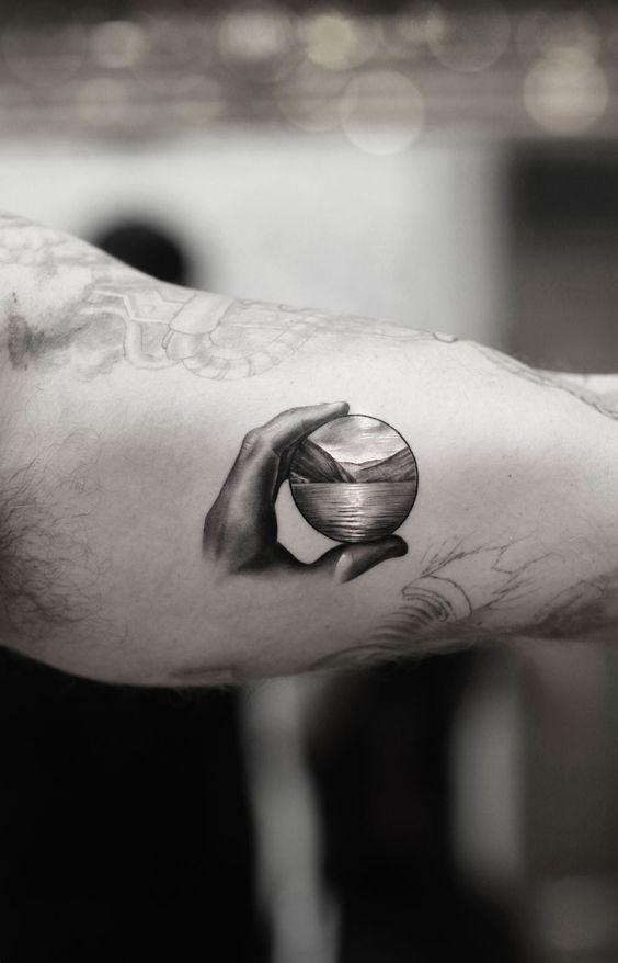 Man wearing a single needle tattoo on his biceps