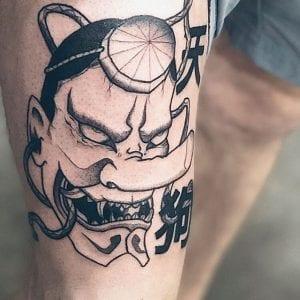 Black and grey Tengu Mask tattoo on the skin