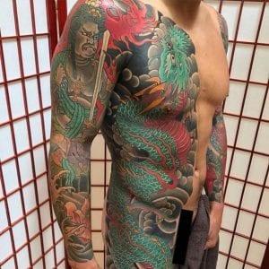 Fudo Myoo sleeve tattoo on the arm