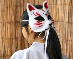 Woman wearing a kitsune mask on the back of her head