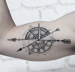 Compass with arrow tattoo on the arm