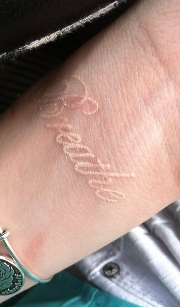 White Ink Lettering Tattoo