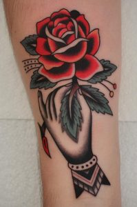 Traditional Hand Holding Flower Tattoo